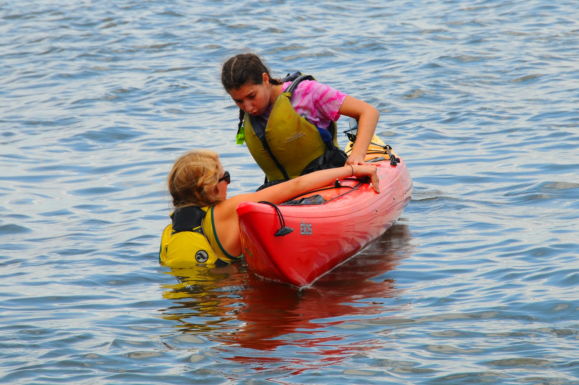 Instructor Lindsay Land (left) shows crew member Alina Zasloff what to do when the kayak flips. (Peter Turcik)