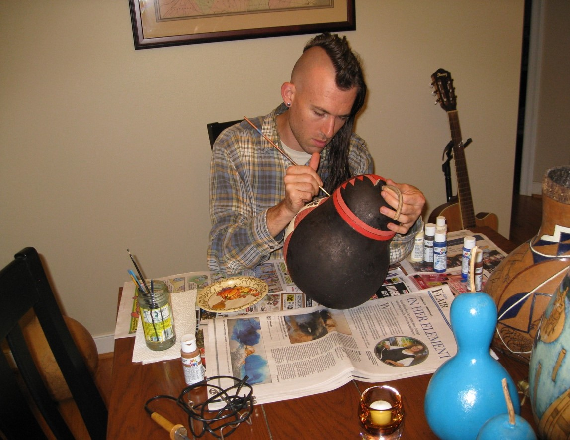 Artist, Ethan Brown painting a gourd.