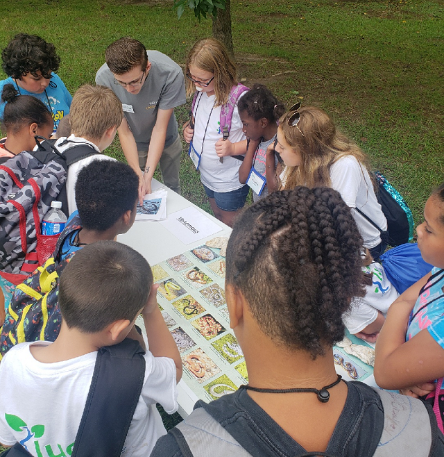 Students standing around a table for a program at Westmoreland State Park.